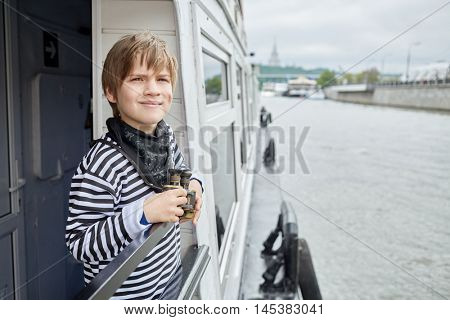 Boy in striped vest with binoculars stands at railings on pleasure boat deck.