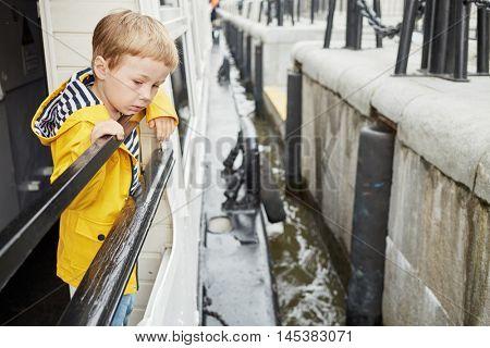 Little boy in yellow jacket on pleasure boat deck looks at boat approaching pier.