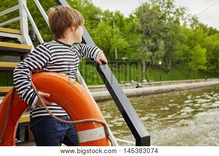 Boy in striped vest with lifebouy ring under his arm stands on pleasure boat deck looking at water.