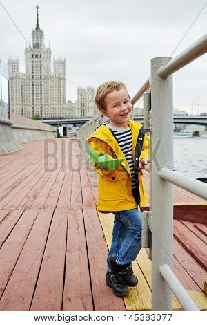 Little smiling boy in yellow jacket stands on embankment holding green paper boat in his hand.