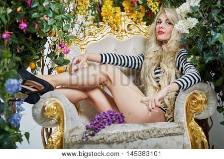 Young blonde woman in striped long sleeve t-shirt sits on a chair surrounded by flowers.