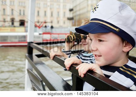 Two little boys one in cap and another with binocular stand on boat stern.