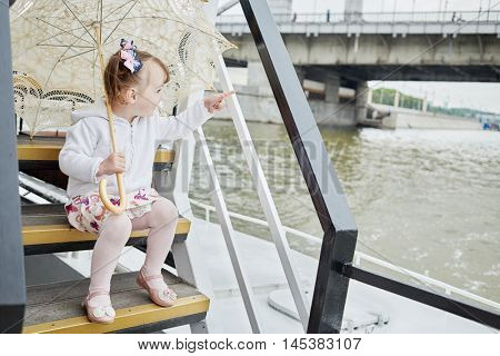 Little girl with umbrella sits on step at pleasure boat deck and points by finger.