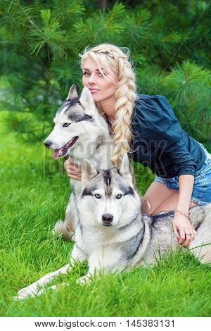 Young blond woman sits embracing two husky dogs on grassy lawn in summer park.