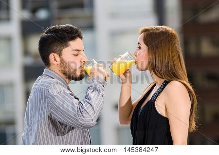 Young attractive couple wearing formal clothes standing on rooftop facing each other drinking from glass with yellow drink, posing for camera, city buildings background.