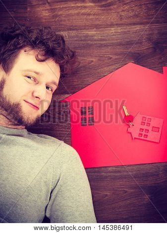 Housing property safety access security ownership property concept. Man lying with house symbols. Young male next to home cutout key ring.