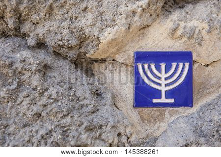 Glazed tile over stone wall with menorah symbol marking the ancient jewish quarter Toledo Spain