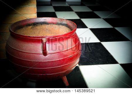 caldeirão vermelho utilizado para festa das bruxas no chão preto e branco