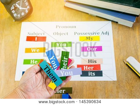 hand holding english words over blur english cards on wooden table