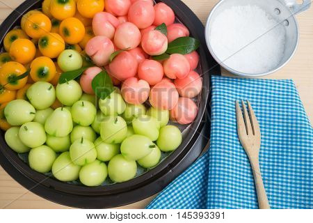 Kitchen table with Thai dessert delectable imitation fruits rose apple orange and peach.