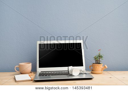 Office desk with laptop Note papercoffee cup and Euphorbia milii flower on terracotta flower pot. View from above notebook keyboard.