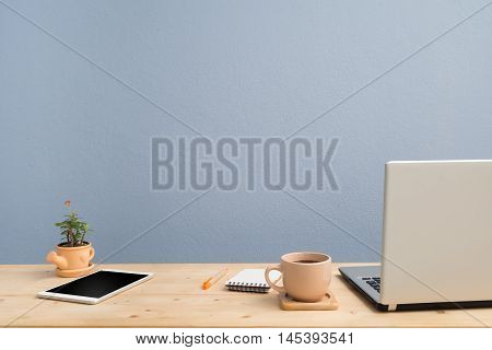Office desk with laptop Note paper Euphorbia milii flower on terracotta flower pot and blank screen tablet.