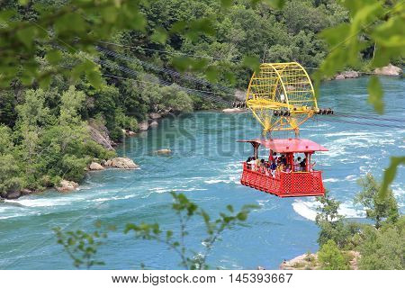 NIAGARA FALLS, CANADA. JUNE 28, 2016. Here we see many tourists suspended over the Mighty Niagara sightseeing and enjoying the ride across the gorge in the Spanish Aero Car.