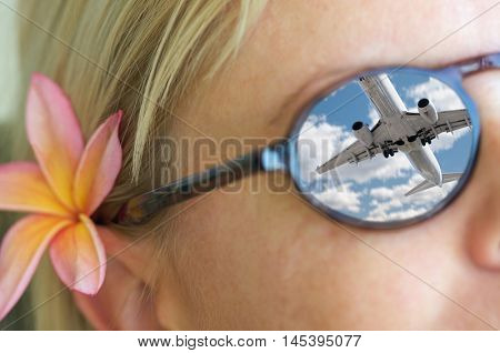 Relaxing Girl Wearing Sunglasses, a Plumeria Flower In Her Hair and Reflection of an Airplane in Her Sunglasses.