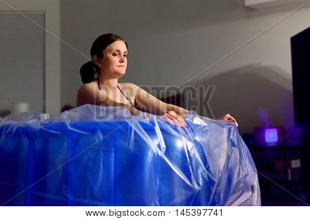 A woman in labor kneels in a birthing tub and pushes back with her arms straight through a contraction.