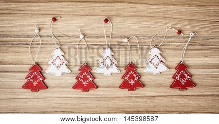 Red And White Ornamental Little Christmas Trees On The Wooden Background