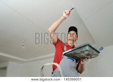 Painting the ceiling and walls. Painter uses paintbrush.
