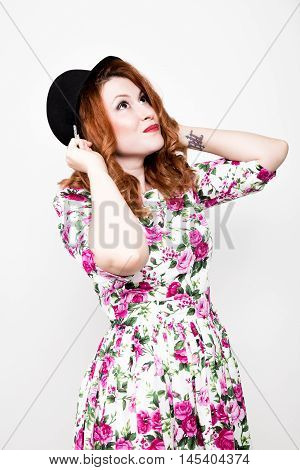 young stylish red-haired woman with curly hair and pretty face holds a black hat. expresses different emotions.