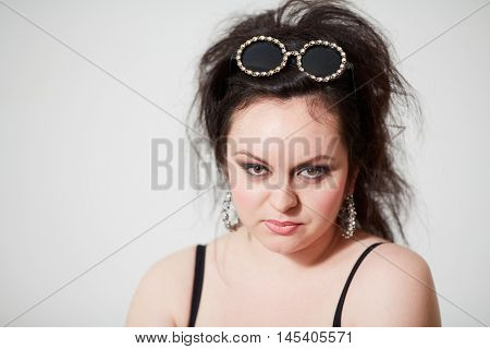 Dark-haired girl model in stylish round dark glasses stares posing in studio.