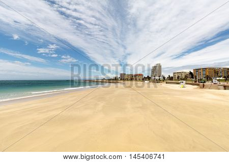 A long deep shot with wide angle to collect the long beach wide sea and a part of the city.