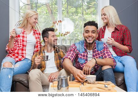Young people drink coffee shop, friends sitting table smiling two couple mix race men women talking