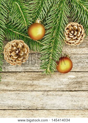 New Year or Christmas background: fir branches goldish glass balls cones over old wooden backdrop top view copy space tinted photo