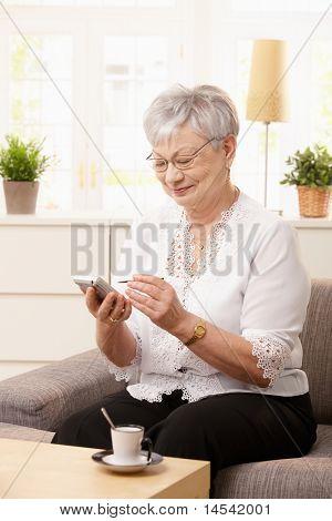 ¿Senior mujer sentada en el sofá, usando palmtop, sonriendo.?