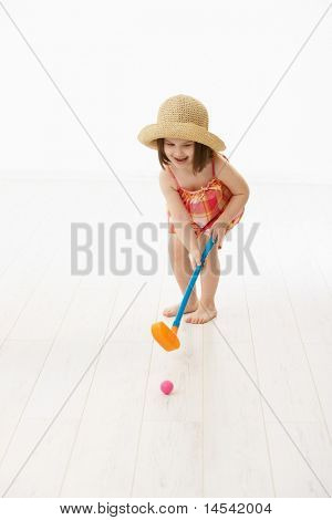 Little girl (4-5 years) in summer dress and straw playing golf indoor. White background.?