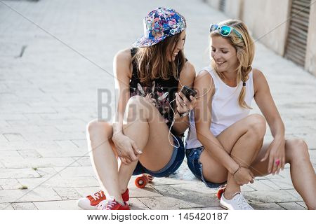 Friends playing music outdoor, seating on skateboard