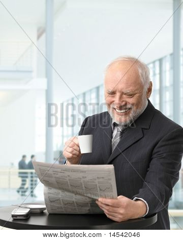 Senior businessman on coffee break in office lobby, reading papers, holding coffee cup, smiling.?