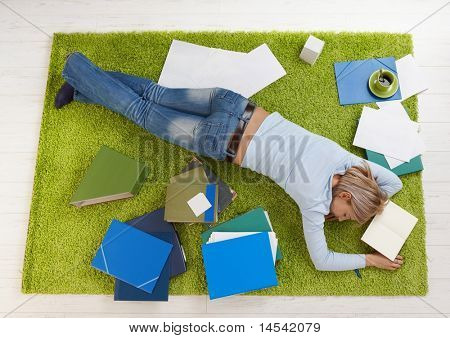Tired college student girl sleeping on floor at home.?