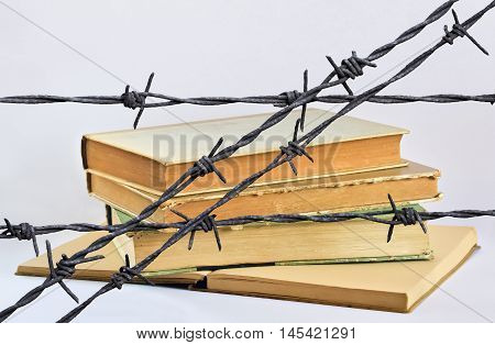 Stack of several old books behind a wire with barbs