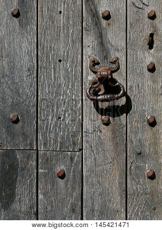 Old Rusty Metal Door Knocker On A Aged Oak Timber Door With Rivets
