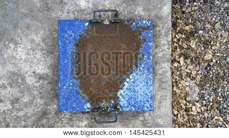 Metal brown rusty manhole cover blue on a pedestrian walkway