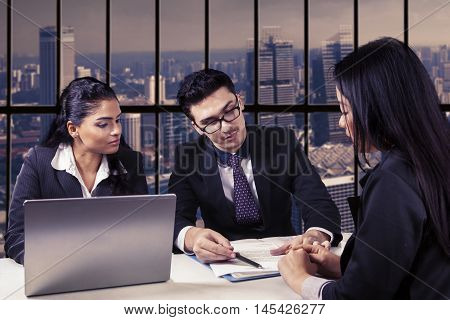 Group of three business people reading an employment contract with laptop on the table in the office