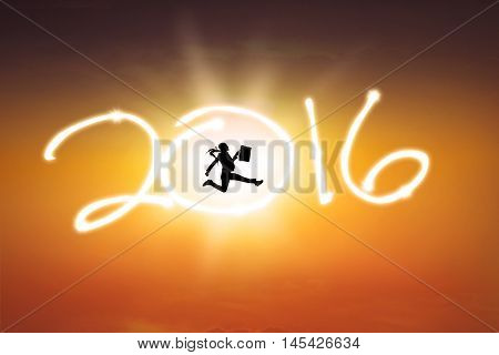 Silhouette of cheerful young businesswoman jumping on the numbers 2016 at sunset time