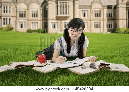 Portrait of a clever Chinese student lying at the park while studying with book and smiling at the camera