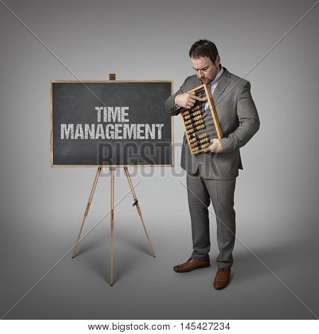 management text on blackboard with businessman and abacus