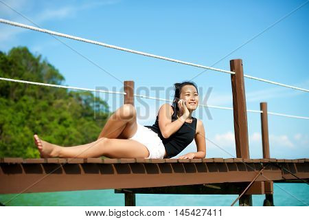 Asian Girl Talking On The Phone At A Pier