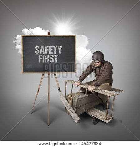 Safety first text on blackboard with businessman and wooden aeroplane
