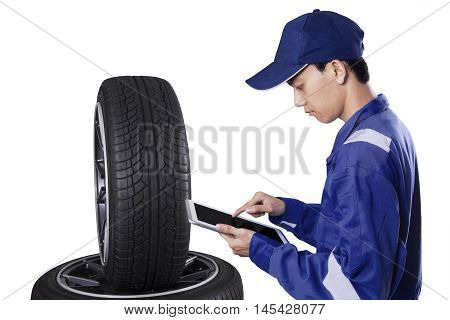 Male mechanic using a digital tablet while checking tires and wearing uniform isolated on white background