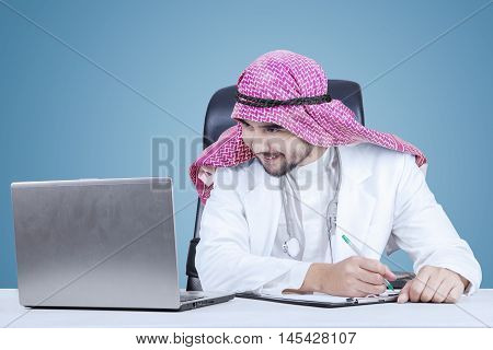 Image of middle eastern doctor writing on the clipboard while looking at the laptop screen