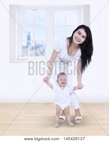 Mother helping baby learn to walk at home