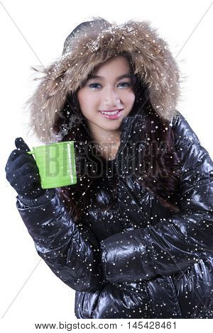 Pretty young woman wears winter fashion smiling at camera while holding mug of hot drink isolated on white background