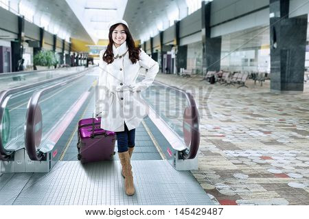 Beautiful young woman wearing winter coat and carrying luggage while standing in the airport hallway