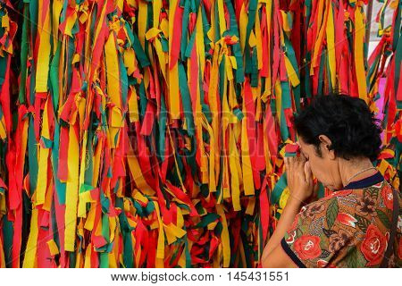 KOH KRED ISLAND, NONTHABURI, THAILAND-SEP 3 2016: People in Thailand are Buddhists, prayer from the Angels are dedicated to the multicolored satin tie against a large tree.
