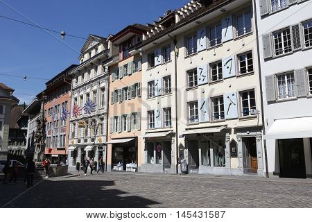 Lucerne Switzerland - May 06 2016: Historic buildings at the Weinmarkt in the combination with decorated fountain in the square show a variety of tourist attractions. These attractively decorated buildings are located almost in the center of the old town