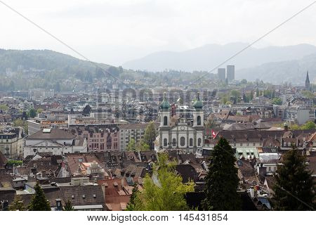 LUCERNE SWITZERLAND - MAY 04 2016: Jesuit Church towering over the houses of the old town. The city shows the unique character and diversity of tourist attractions
