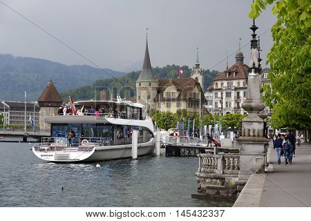 LUCERNE SWITZERLAND - MAY 03 2016: The city seen from the Lake Lucerne. At the ferry terminal MS Saphir is moored. It is elegant Panorama-Yacht that offers breathtaking tours of the lake