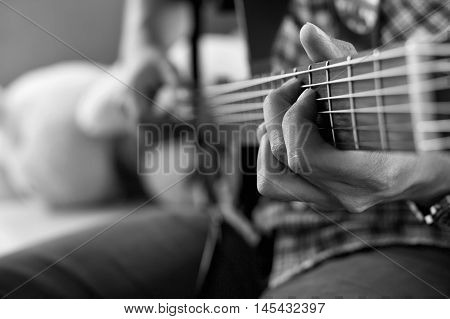 playing acoustic guitar barre chordselective focusblack and white tone.